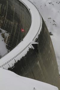 Swiss flag over snowy dam Switzerland