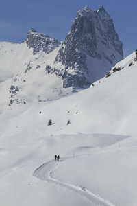 People snowshoeing on sunny  snow covered mountain  Switzerland