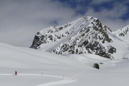 Snowshoer on sunny snowy mountain  Switzerland