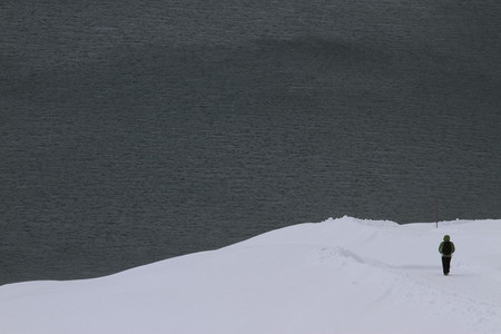 Snowshoer on snowy slope overlooking lake