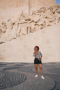Stylish woman in sunglasses below Monument to the Discoveries Lisbon Portugal
