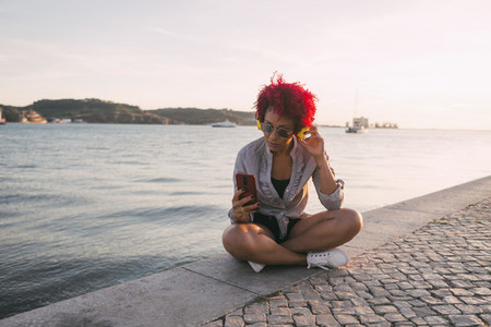 Woman with red hair listening to music with headphones and smart phone at waterfront