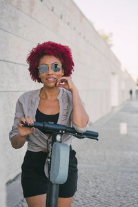 Portrait confident woman using shared public electric push scooter