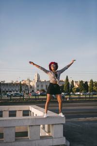 Portrait confident carefree woman on building ledge
