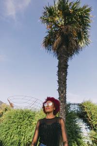 Stylish woman wearing sunglasses below sunny palm tree