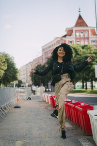 Portrait carefree young woman dancing on city sidewalk