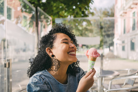 Carefree excited young woman enjoying pink ice cream cone