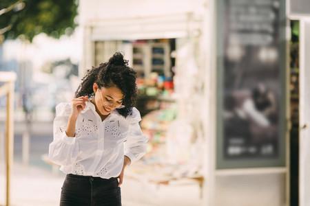 Happy young woman walking on urban sidewalk