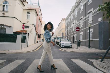 Portrait happy stylish woman crossing city street