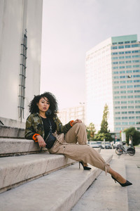Portrait confident stylish woman on urban steps