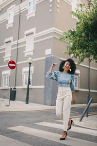 Portrait happy  carefree woman crossing city street