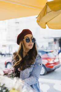 Young woman in beret and sunglasses shopping for flowers on urban sidewalk