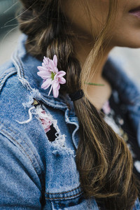 Close up young woman with purple flower in braided hair