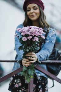 Portrait young woman holding purple flower bouquet