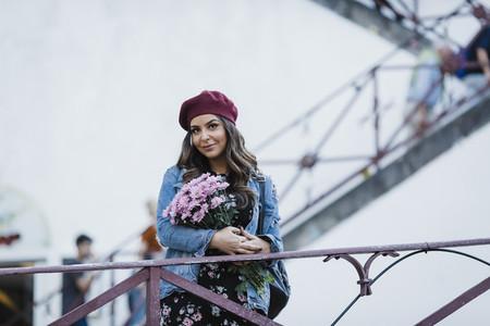 Portrait woman in beret holding flower bouquet