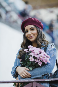 Portrait smiling young woman in beret holding flower bouquet