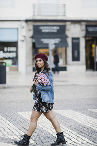 Portrait confident young woman crossing city street with bouquet of flowers