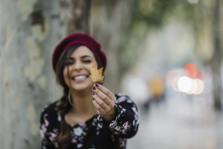 Portrait happy young woman holding autumn leaf