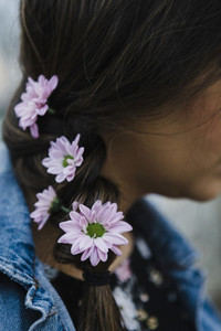 Close up woman with purple flowers in braided hair