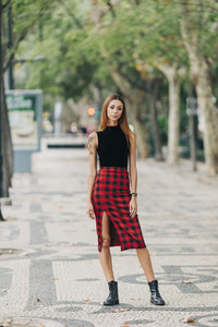 Portrait confident  stylish young woman wearing checked skirt in urban park