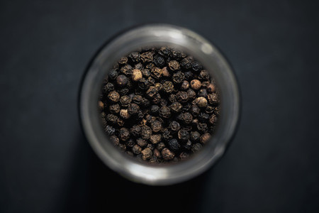 View from above black peppercorns in spice jar