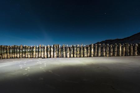 Sheet piling wall illuminated on beach at night