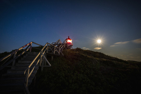 Illuminated lighthouse under full moon night sky