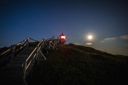 Illuminated lighthouse under full moon night sky