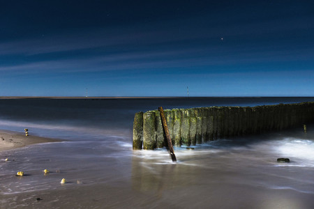 Ocean retaining wall illuminated at night
