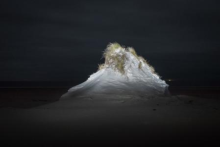 Sand dune illuminated at night
