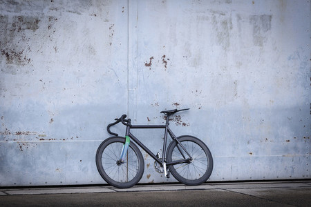 Racing bicycle leaning against concrete wall