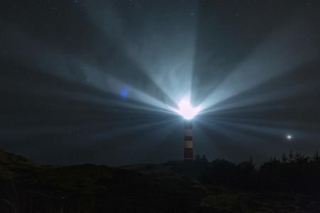 Light beacons illuminating from lighthouse under starry night sky