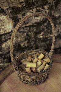 Wine corks in rustic basket on keg
