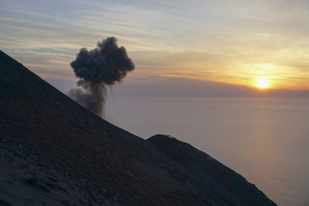 Ash plume rising along tranquil sunset ocean view
