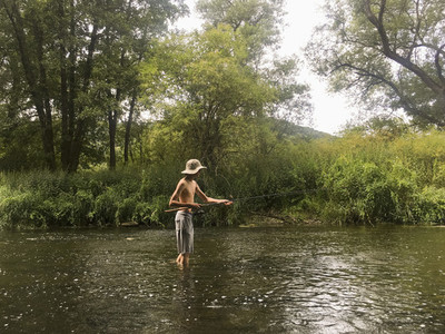 Boy fishing in rural river