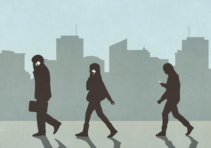 Pedestrians walking and using smart phones in city