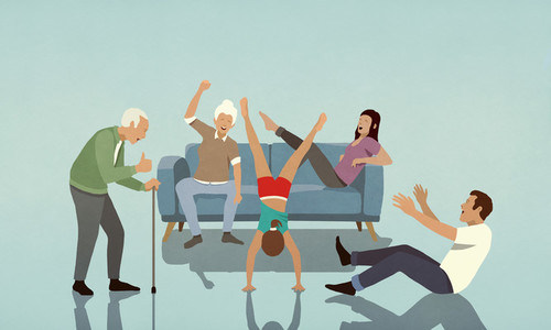 Happy multi generation family cheering for girl doing handstand in living room