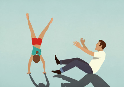 Happy father cheering for daughter doing handstand