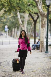 Smiling female tourist pulling suitcase along treelined sidewalk