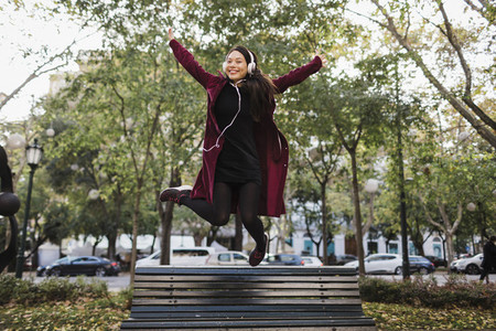 Portrait playful exuberant woman jumping off urban city bench
