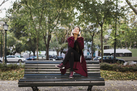 Carefree woman listening to music with headphones on urban park bench