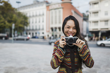 Portrait confident  carefree female tourist using camera on city street