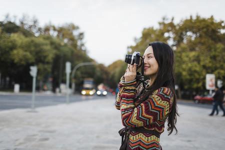 Female tourist using camera on city street