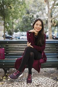 Portrait smiling  stylish woman on park bench