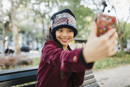 Happy woman taking selfie with camera phone on park bench