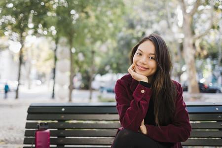Portrait happy woman on park bench