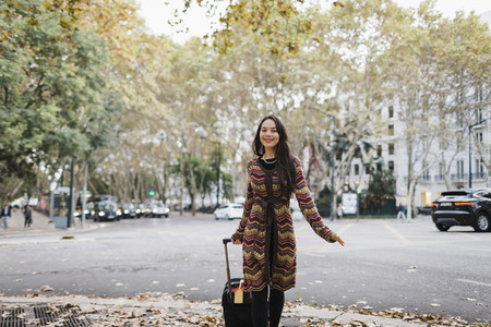 Portrait happy female tourist with suitcase on urban autumn street