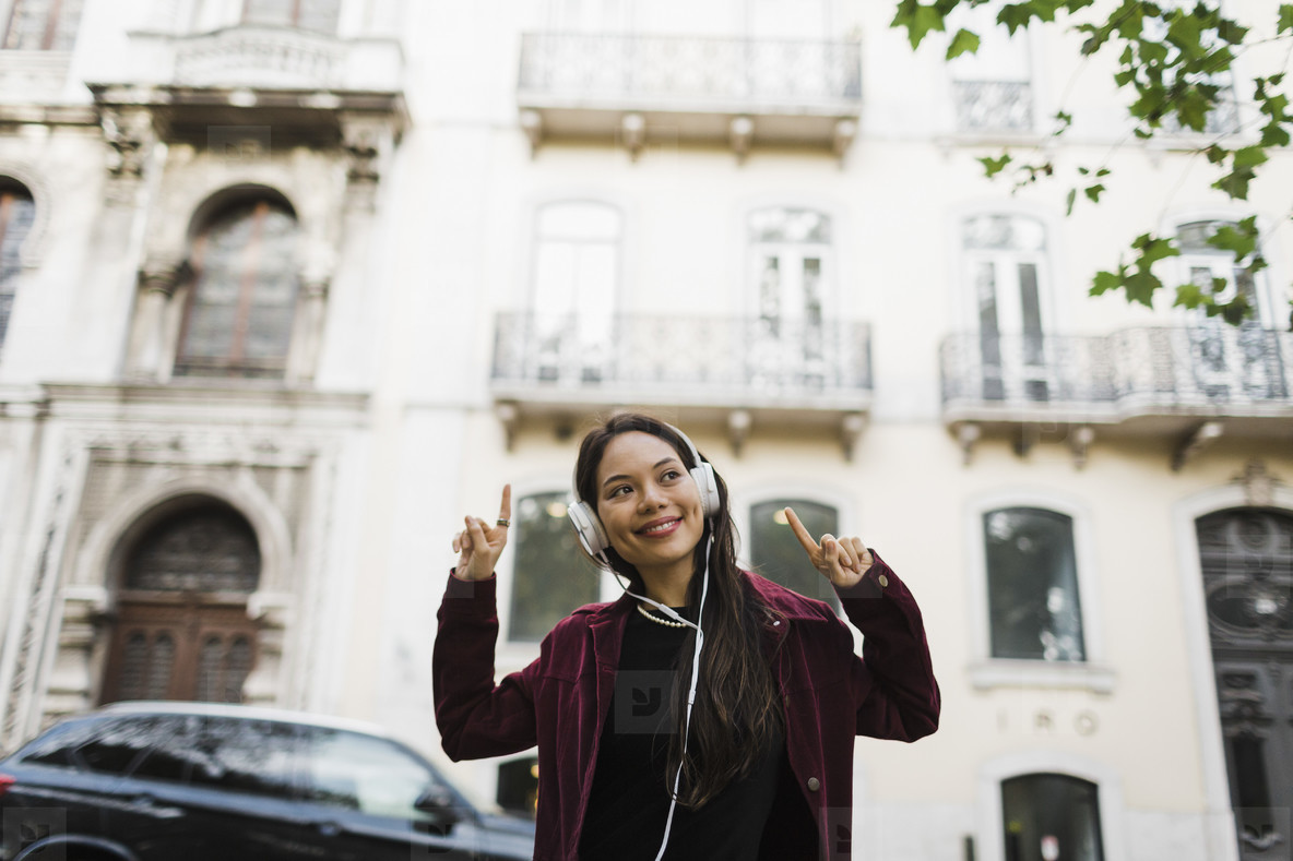 Portrait playful  cool woman listening to music with headphones on urban street