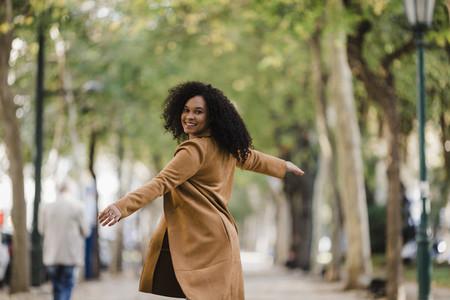 Portrait carefree young woman dancing on treelined sidewalk