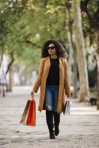 Stylish young woman walking with shopping bags on sidewalk